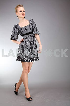 Beautiful young woman in light dress with gray background