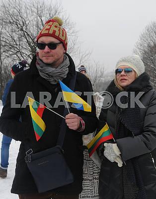 Люди держат флажки Литвы и Украины