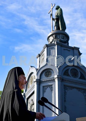 Priest near the monument to Vladimir