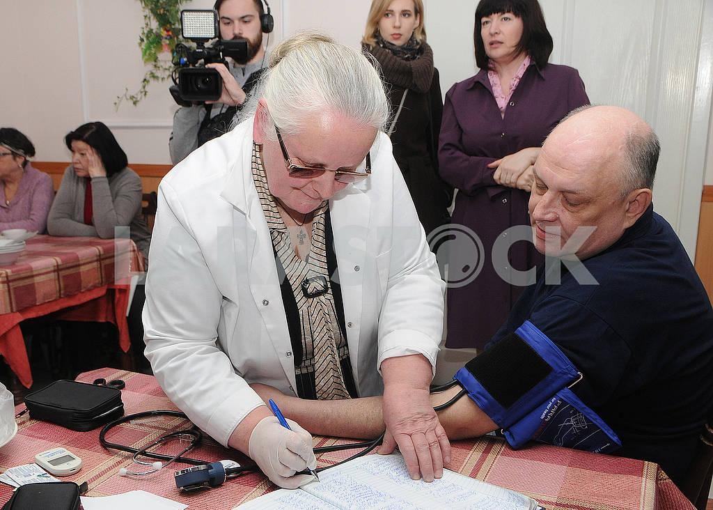 Медицинский работник измеряет давление мужчине — Изображение 73146