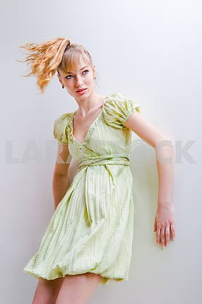Girl in a green dress. In the studio