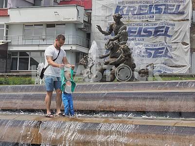 Мужчина и мальчик в фонтане