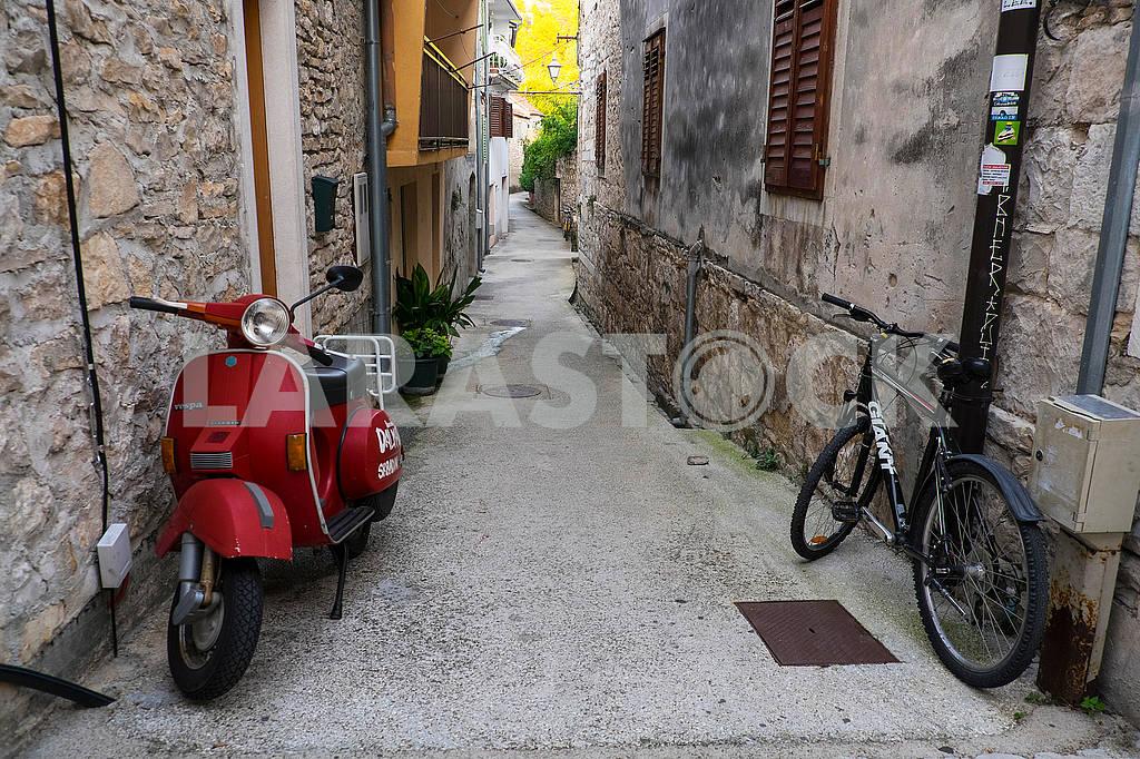 Скутер и велосипед на узкой улочке в Скрадине — Изображение 74707