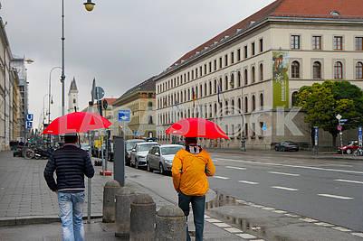 Men under red umbrellas