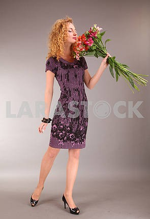 beautiful young woman in light dress with flowers on gray backgr
