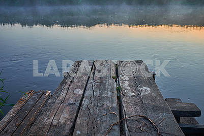 The old ancient wooden layer on river during the foggy sunrise