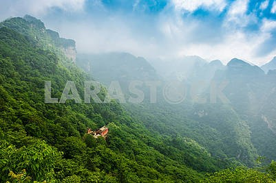 Foggy sunrise on top of mountain over the ancient asian building