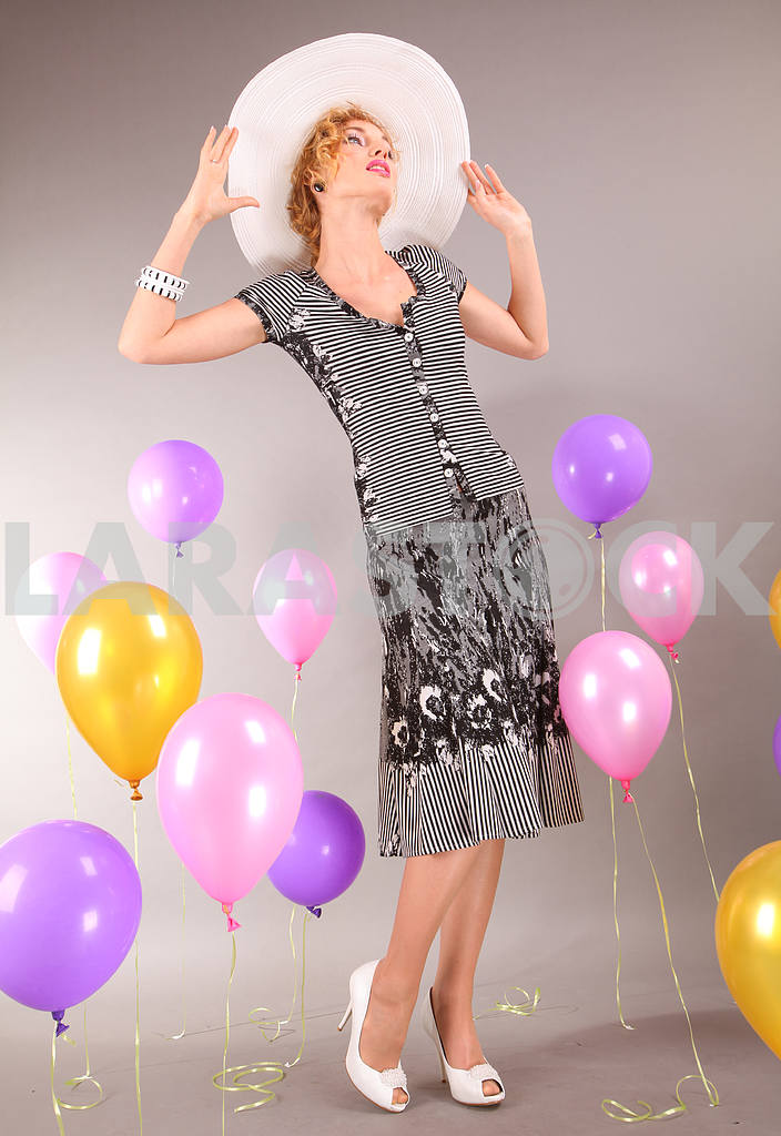 Beautiful young girl in light dress a hat on background balloons — Image 7658