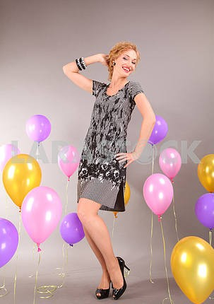 Beautiful young girl in light dress on background balloons