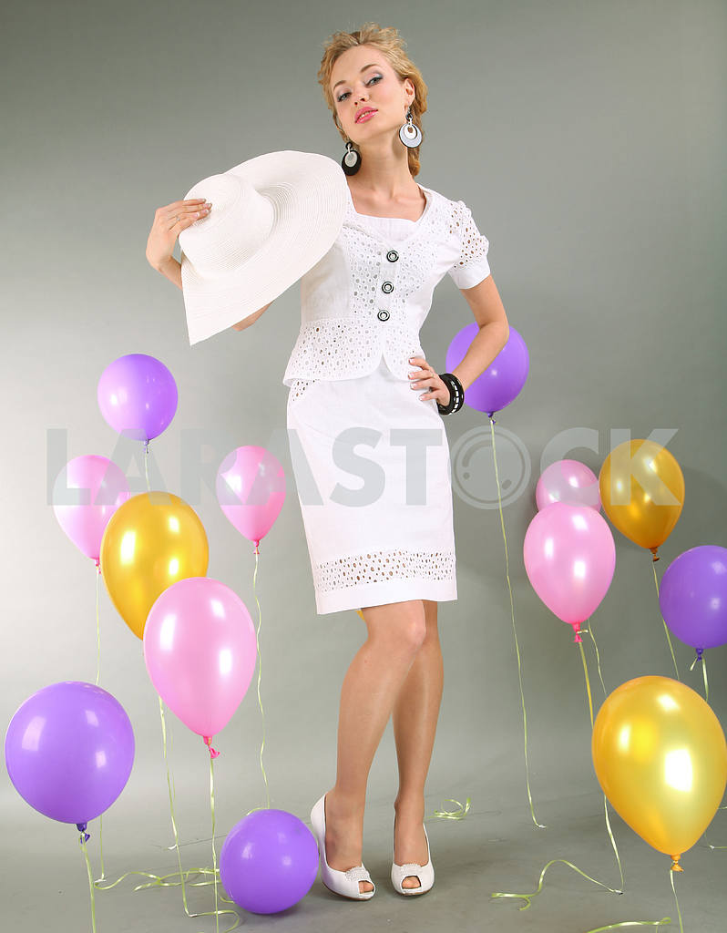 Beautiful young girl in light dress a hat on background balloons — Image 7729