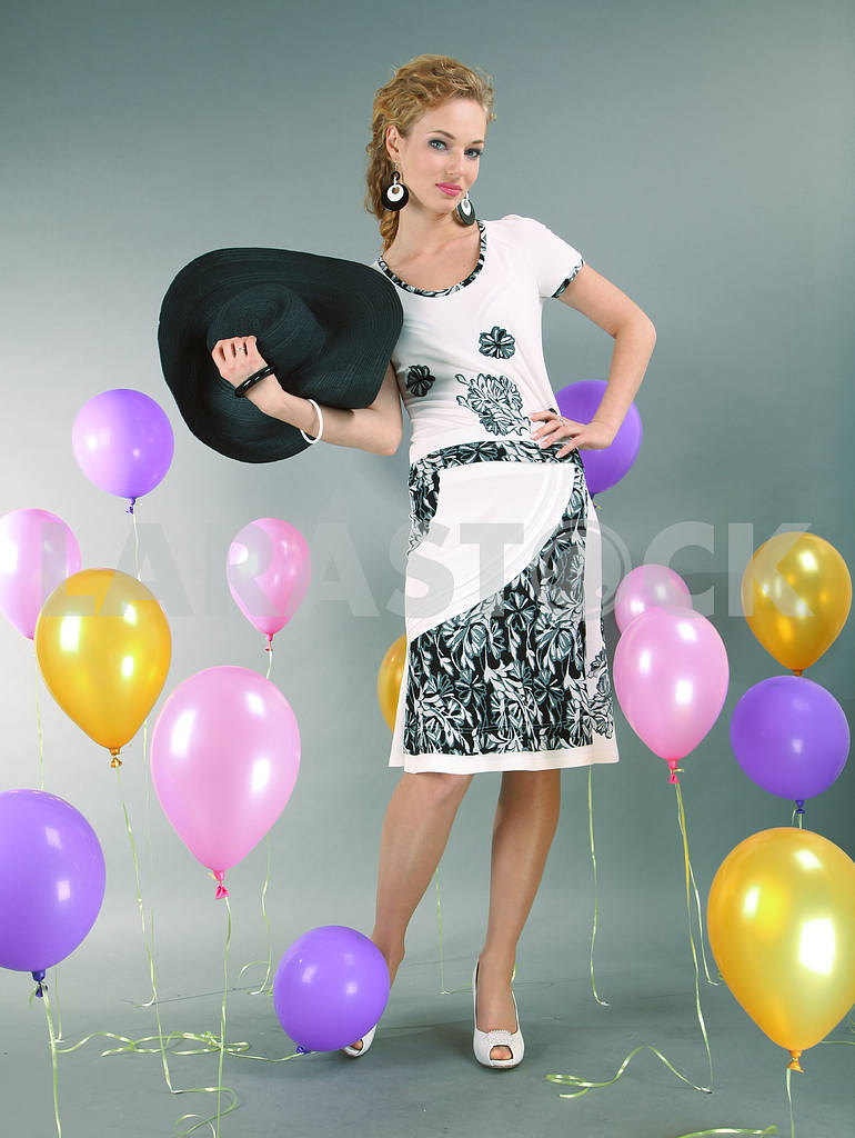 Beautiful young girl in light dress a hat on background balloons — Image 7730