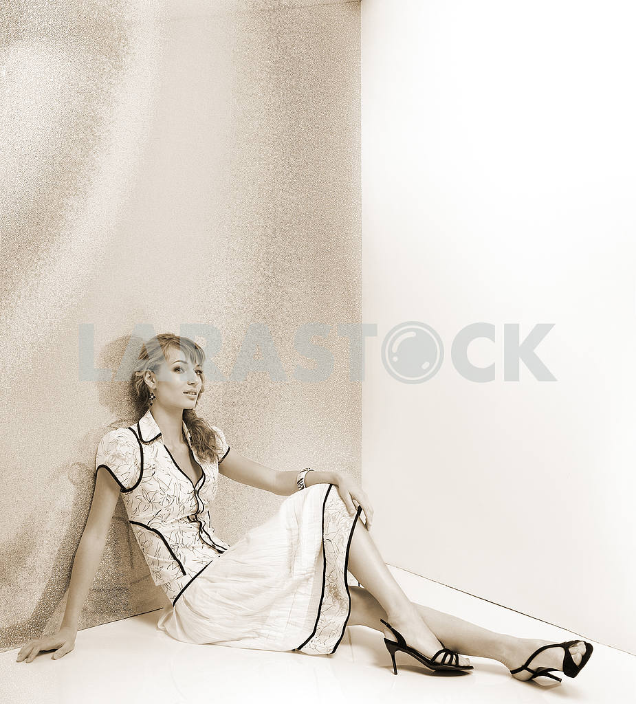Beautiful girl in white dress sitting on the floor. In black sho — Image 7751