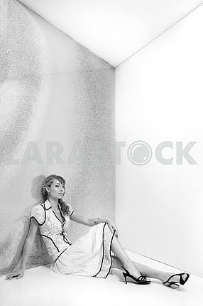 Beautiful girl in white dress sitting on the floor. In black sho