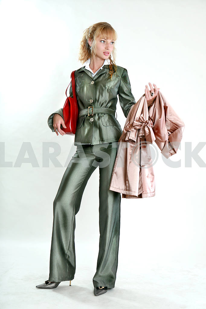 Beautiful Young Woman in gray suit. With a red bag and coat. In  — Image 7757