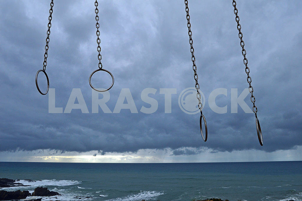 Gymnastic rings on the beach against the background of a thunderstorm sky — Image 77939