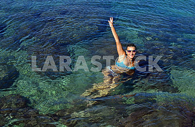 A young woman in swimsuit floats in seawater