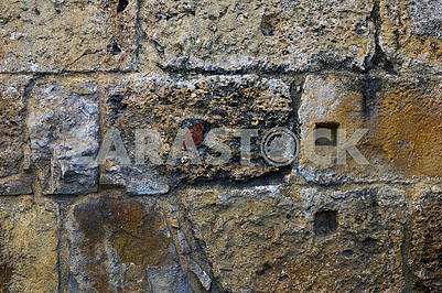 A fragment of the surface of the wall is constructed of stone blocks
