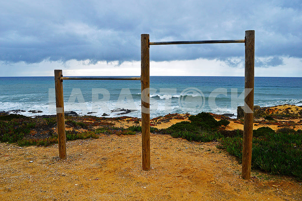 Gymnastic bar on the beach against the background of a dark stormy sky — Image 78269