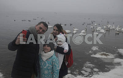 People are photographed against a background of swans.