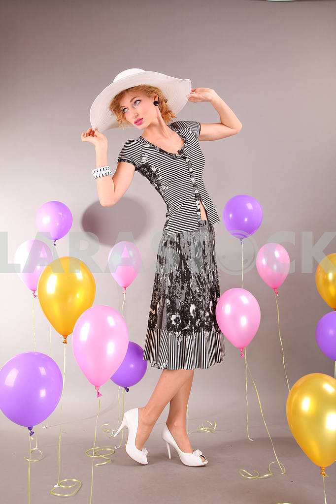 Beautiful young girl in light dress a hat on background balloons — Image 7904