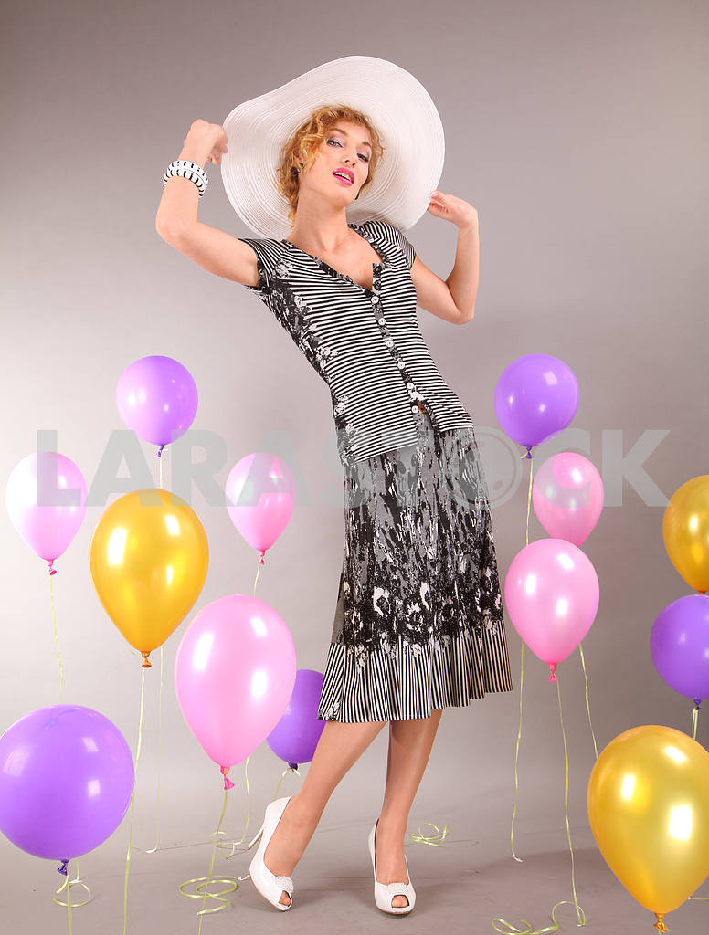 Beautiful young girl in light dress a hat on background balloons — Image 7905