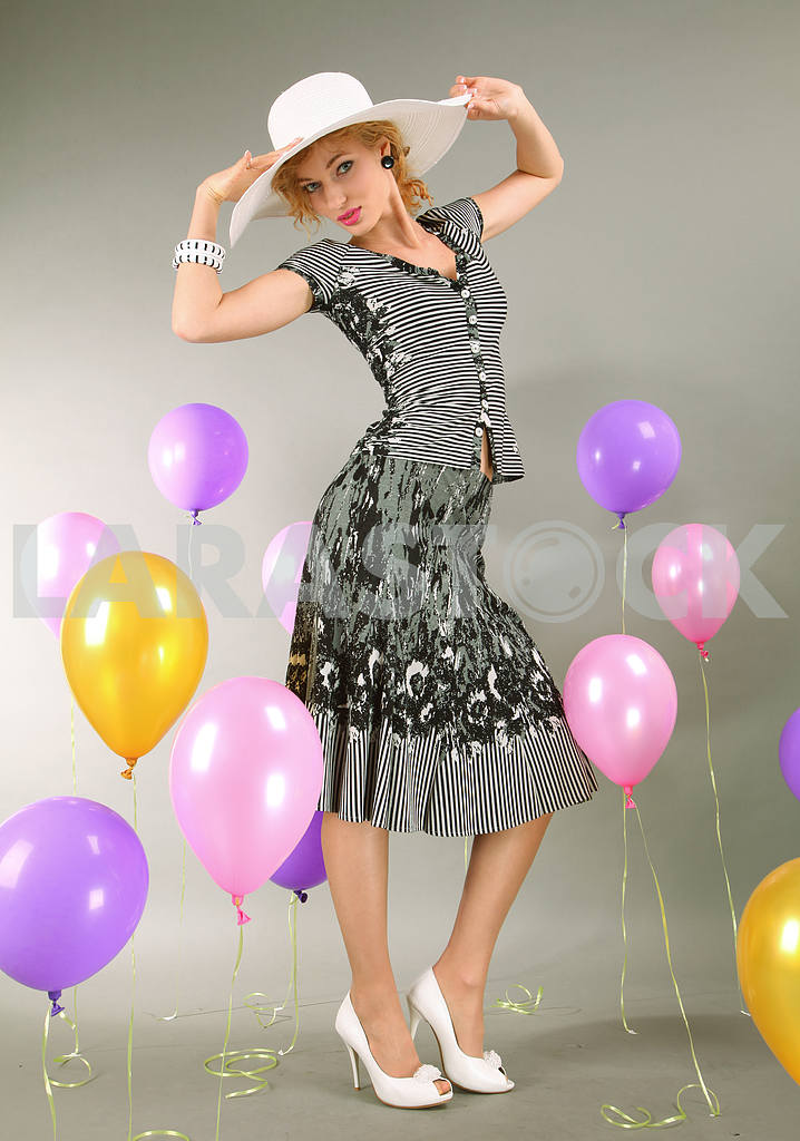 Beautiful young girl in light dress a hat on background balloons — Image 7906
