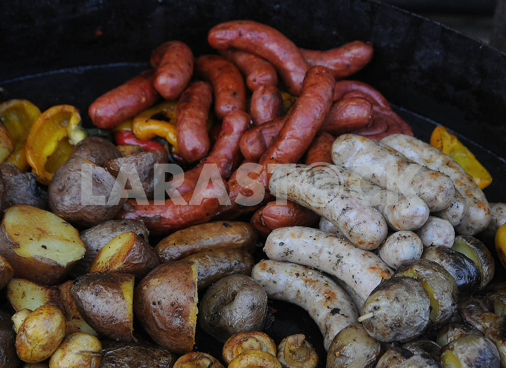 Baked potatoes and fried sausages in a pan — Image 79593