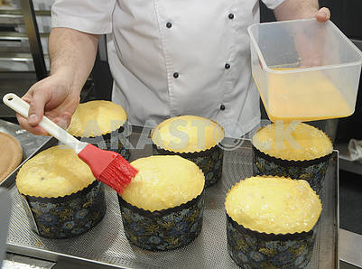 Cook covers Easter cakes with egg yolk