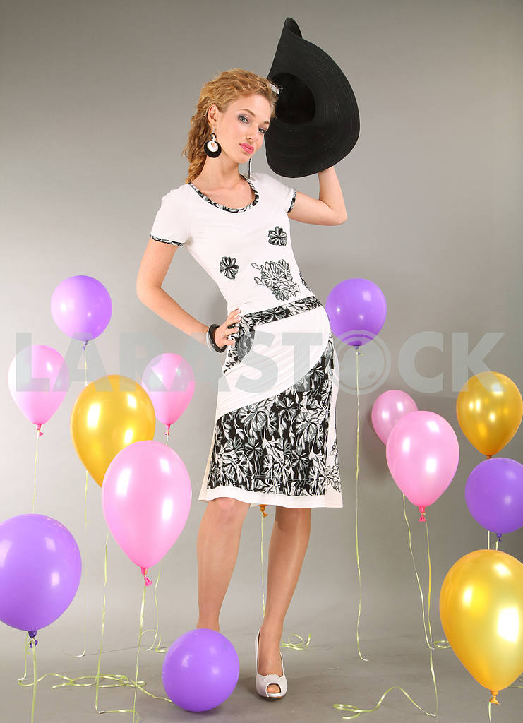 Beautiful young girl in light dress a hat on background balloons — Image 7981