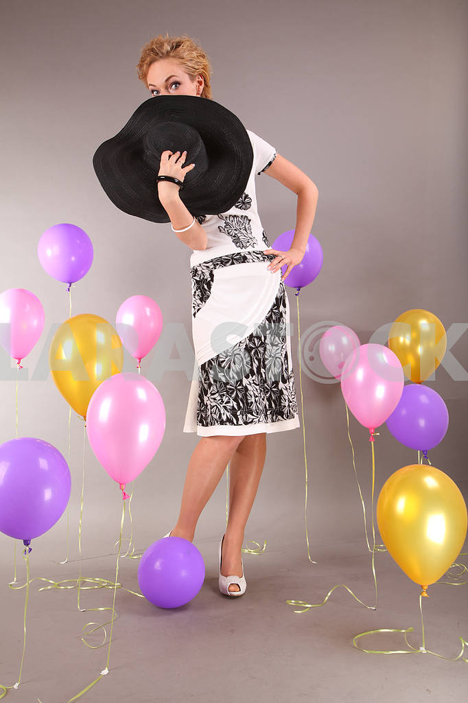 Beautiful young girl in light dress a hat on background balloons — Image 7983
