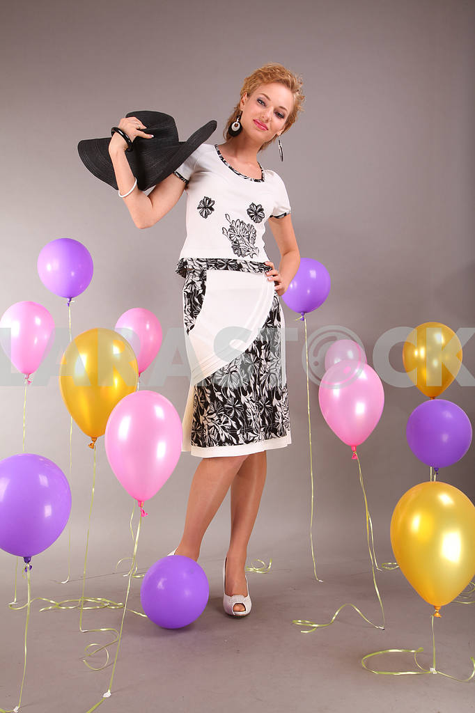 Beautiful young girl in light dress a hat on background balloons — Image 7984