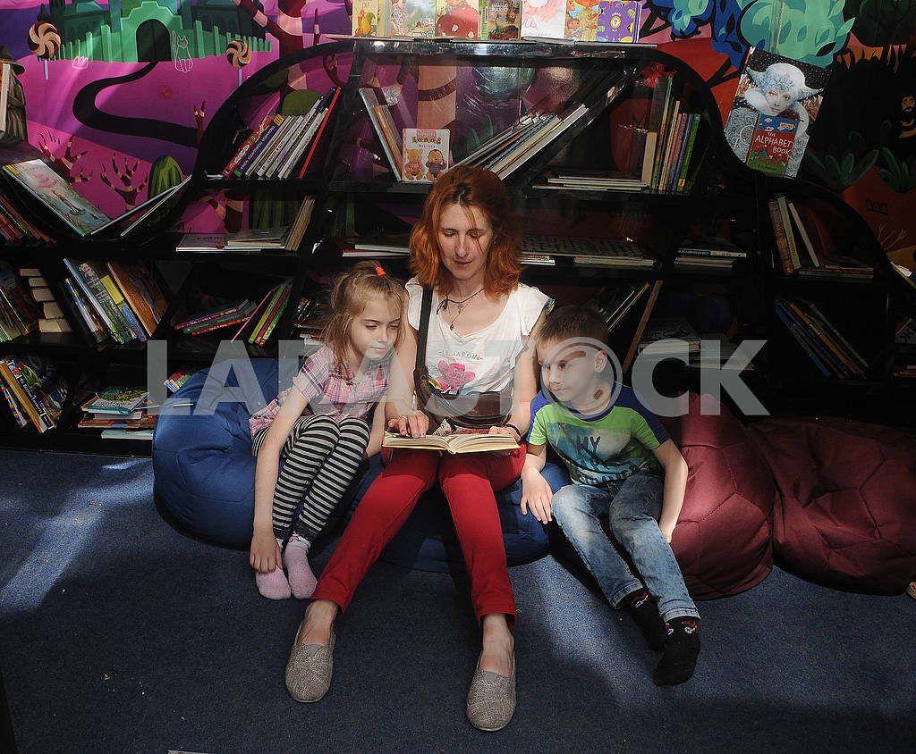 A woman is considering a book with children — Image 80093