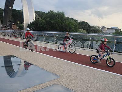 Дети на велосипедах едут по мосту