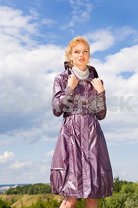 Beautiful Young Woman in coats. Against the backdrop of blue sky