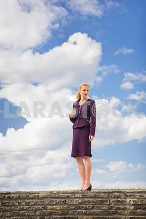 Красивая молодая женщина в костюме, против фоне ярко- п