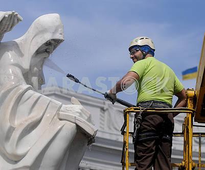 Работник клининговой компании моет памятник Кириллу и Мефодию