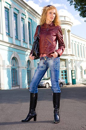 Beautiful Young Woman in jacket, blue jeans end boots. Against t