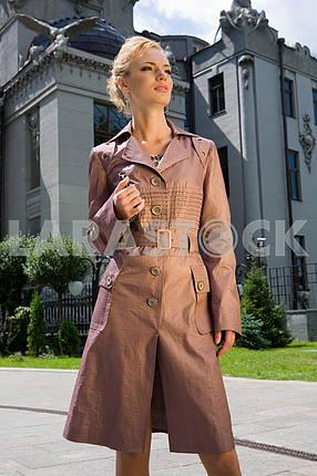 Красивая молодая женщина в коричневом плаще . На фоне