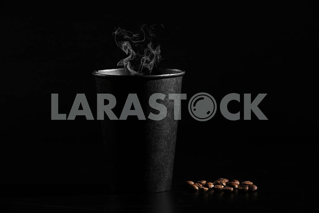 A black glass of hot coffee with scattered coffee beans on a black background. close-up — Image 80631
