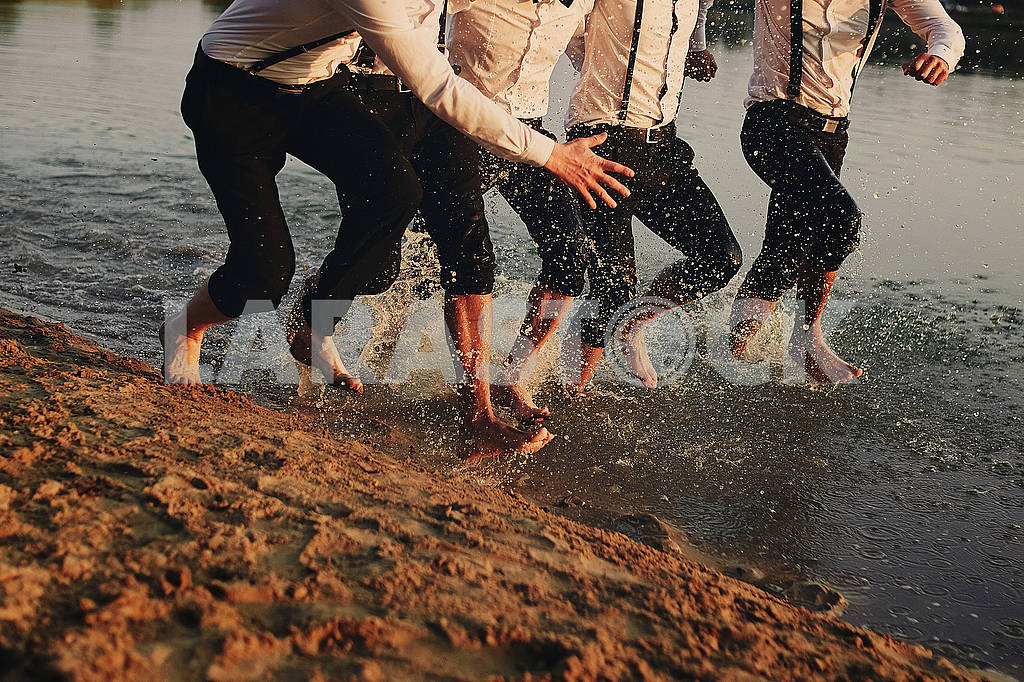 Men's feet in the water. They are having fun, playing and splashing water around them. men in costumes run on water. summer. group of happy young man feet splash water — Image 80639