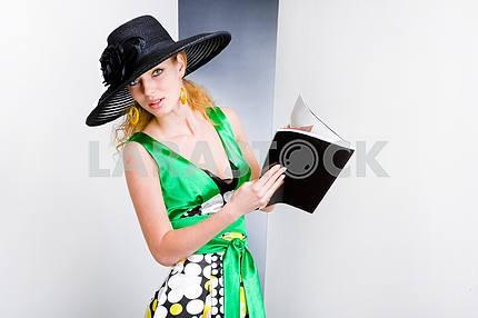 Молодая женщина в зеленом платье и черной шляпе . В студии