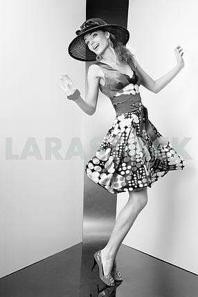 Молодая женщина в платье и черной шляпе . Во всех роста. В студии