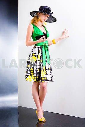 Young Woman in a green dress and black hat. In all growth. In th
