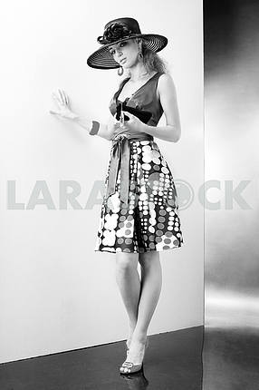 Young Woman in dress and black hat. In all growth. In the studio