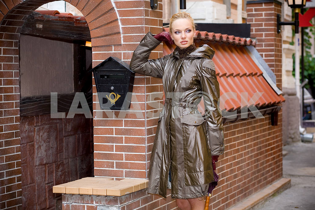 Beautiful Young Woman in coat. Against the backdrop of  building — Image 8129