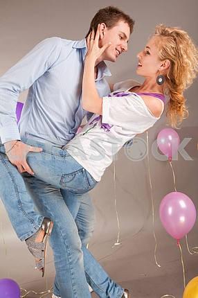 Молодые любви пара улыбается с воздушными шарами