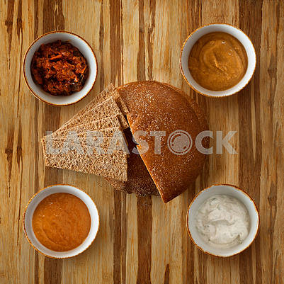 flatlay traditional dark bread loaf on a plate with slices, with