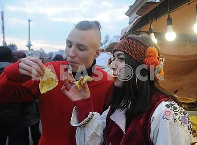 Мужчина и женщина в национальных костюмах едят блины