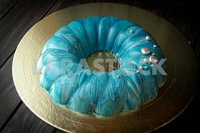 blue berry mousse cake, covered with a turquoise mirror glaze with sea effect.