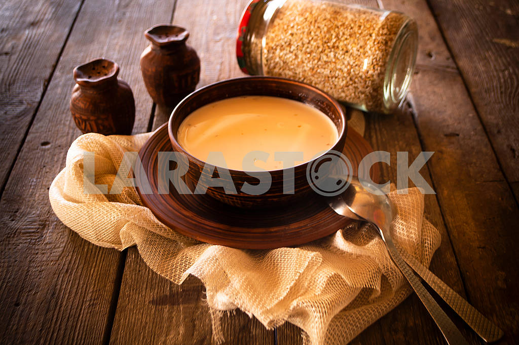 Boiled buckwheat with milk in wooden bowl on rustic wooden background — Image 83010